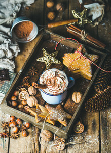 Mug of hot chocolate gingerbread cookies nuts in wooden tray