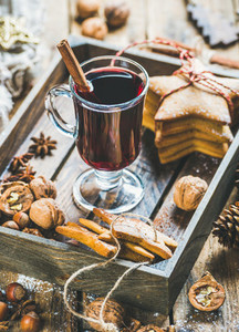Glass of mulled wine with gingerbread cookies  nuts  spices