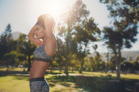 Fit young woman getting ready for workout at the park