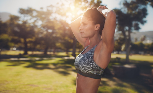 Muscular young woman exercising at the park