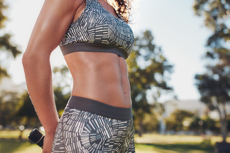 Muscular torso of a sportswoman at the park