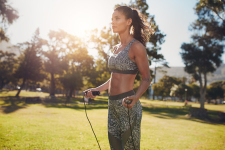 Determined woman exercising with jump rope in nature
