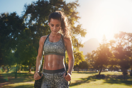 Fit and athletic woman in park with a jump rope
