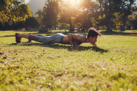 Fitness woman doing push ups exercise in a park