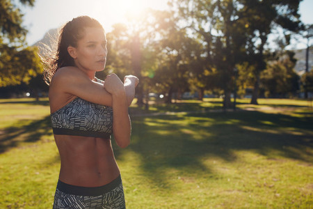 Athletic woman stretching arms before workout