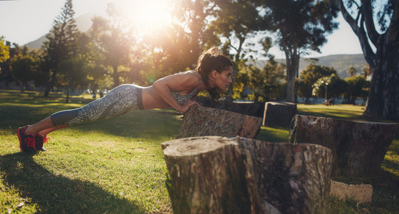 Tough young woman doing pushups on a log at park