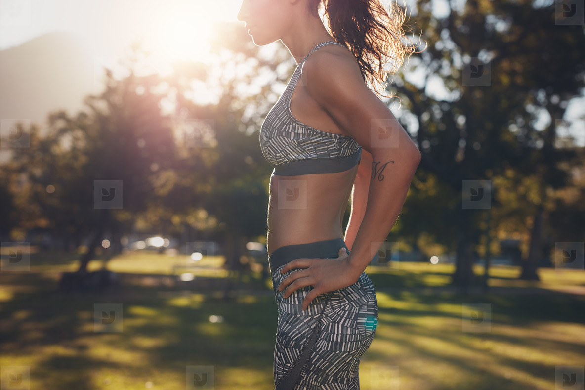 Fit woman athlete in sportswear standing at a park