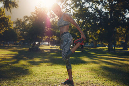 Healthy young woman stretching in a park