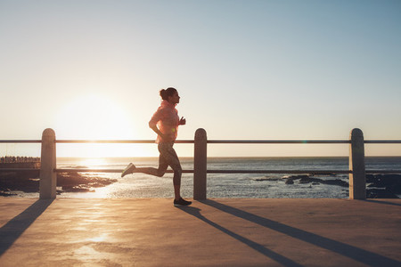 Fit and young woman running on the seaside road