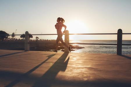 Young woman running on seaside promenade