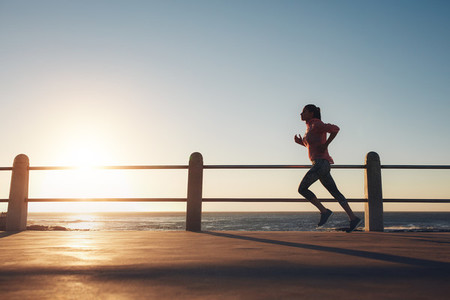 Sportswoman running on a road by the sea