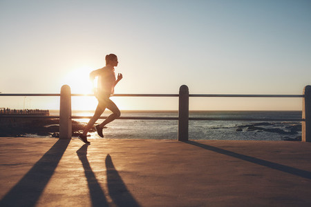 Sportswoman training on seaside promenade at sunset