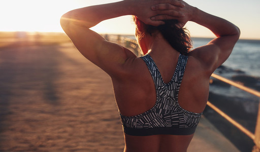 Muscular woman in sports bra at sunset