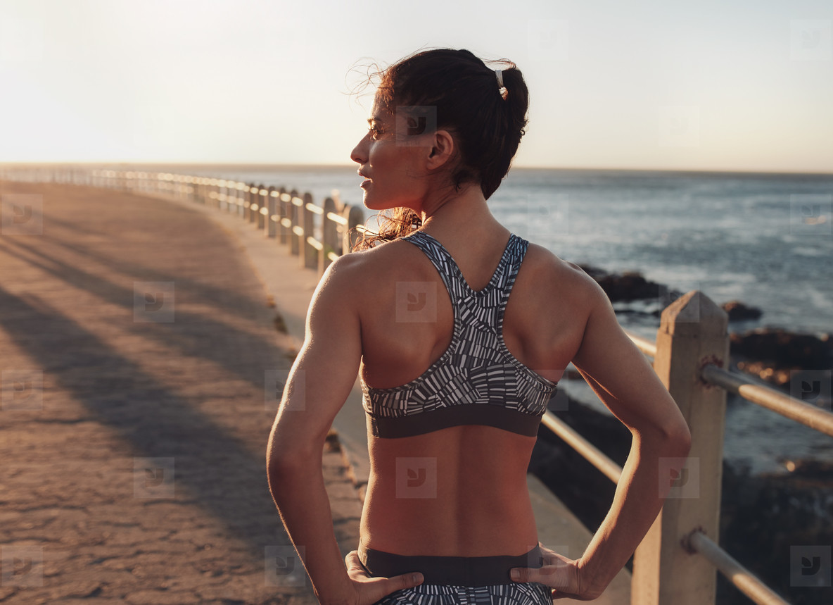 Fitness woman standing on a seaside promenade