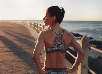 Fitness woman standing on a seaside promenade