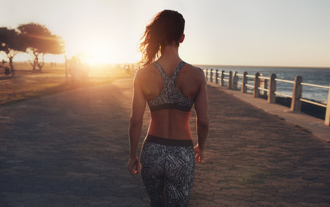 Fitness woman walking on a seaside promenade at sunset
