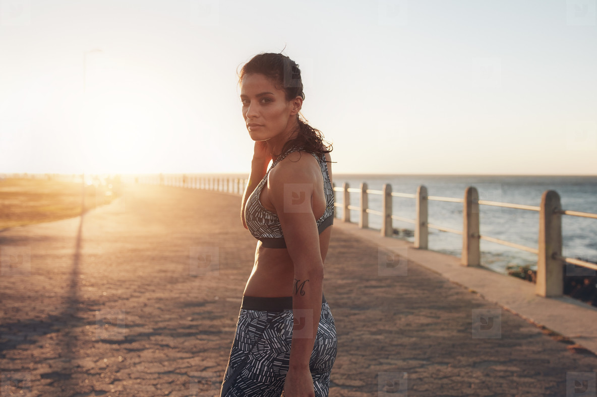 Muscular young woman in sportswear walking by the sea