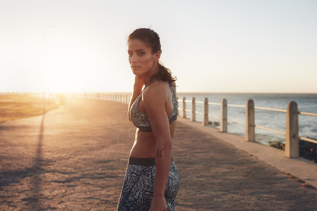 Muscular young woman in sportswear walking by the sea