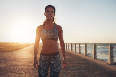 Confident sportswoman standing on a seaside road at evening