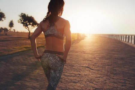 Sportswoman walking on a seaside promenade at sunset