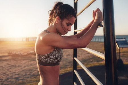 Tired young fitness woman leaning to wall bars outdoors