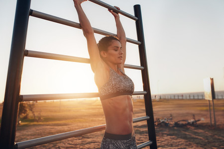 Young woman exercising on wall bars outdoors
