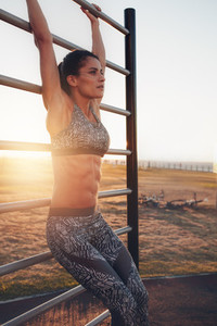 Fit young woman training outdoors on wall bars