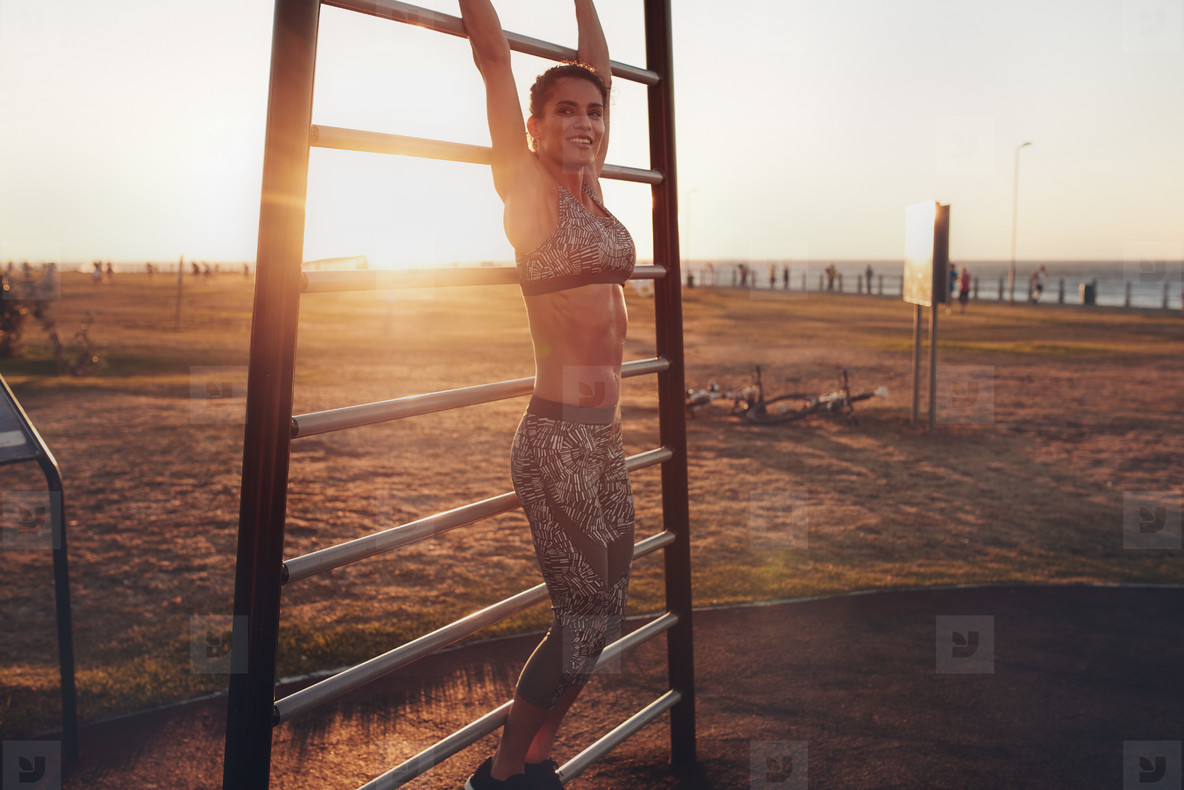 Young female exercising on wall bars outdoors