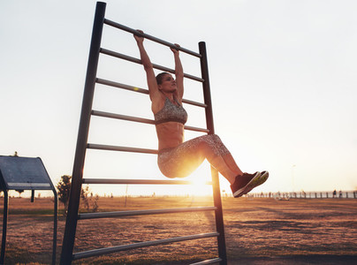 Fitness woman exercising on wall bars outdoors