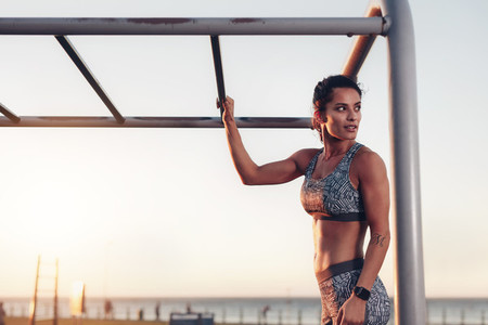 Muscular woman standing by monkey bars