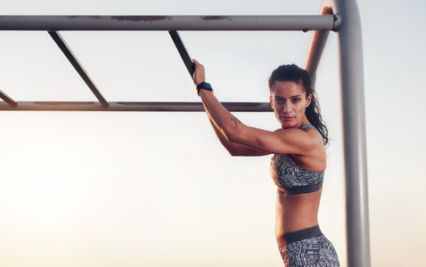 Fitness woman training outdoors on monkey bars