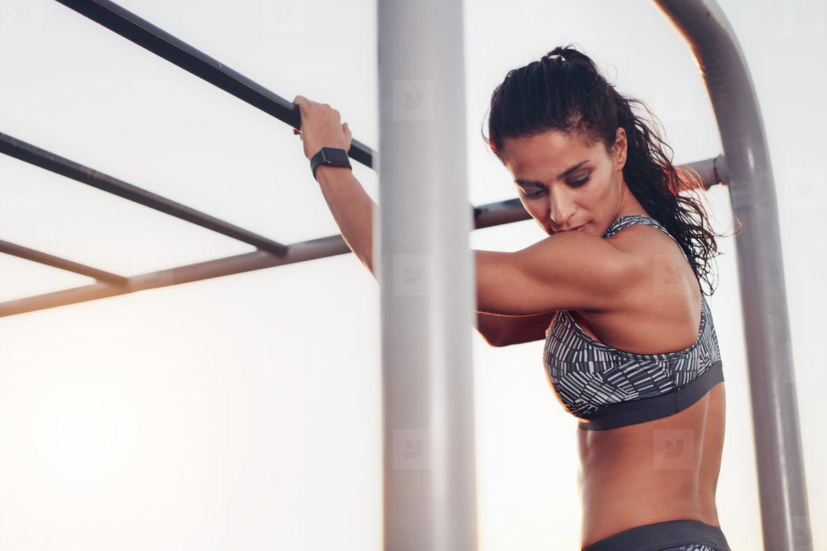 Female athlete standing by monkey bars