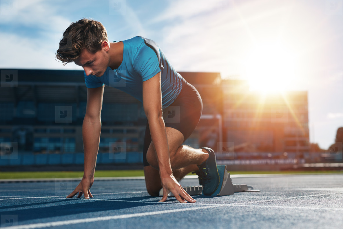 Athlete at starting block on running track