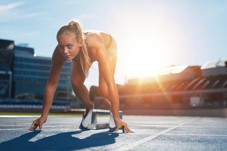 Professional female track athlete on sprinting blocks