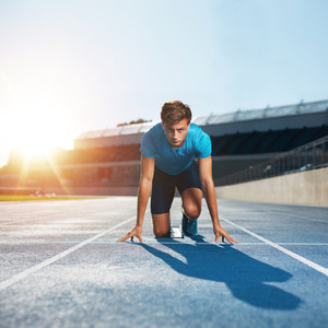Fit and confident sprinter at starting blocks