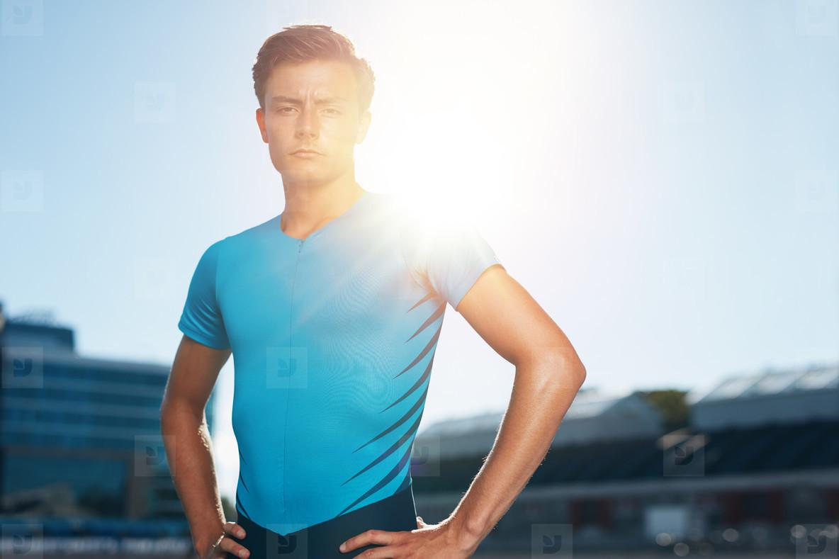 Confident male athlete standing in stadium