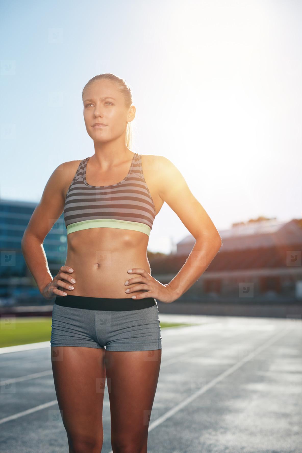 Confident athlete on athletics racetrack