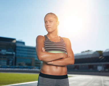 Young woman in sportswear standing on racetrack