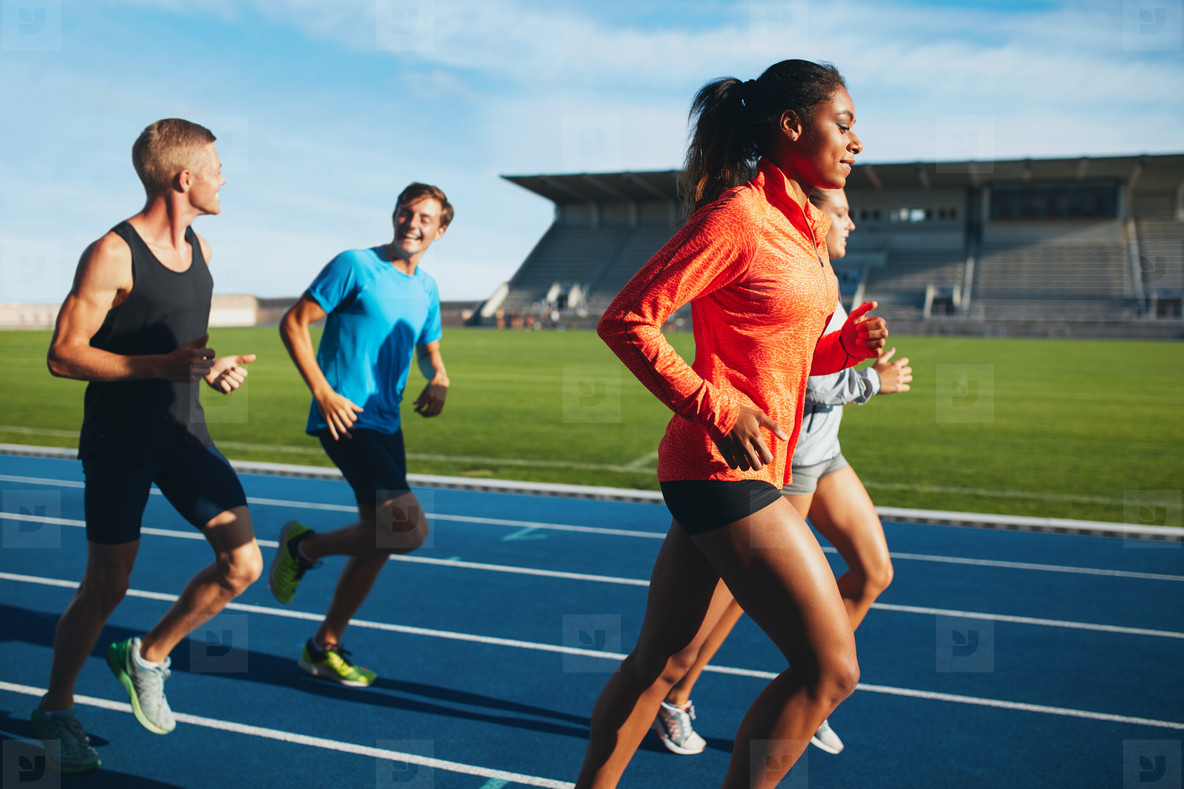 Fit men and women running on a race track