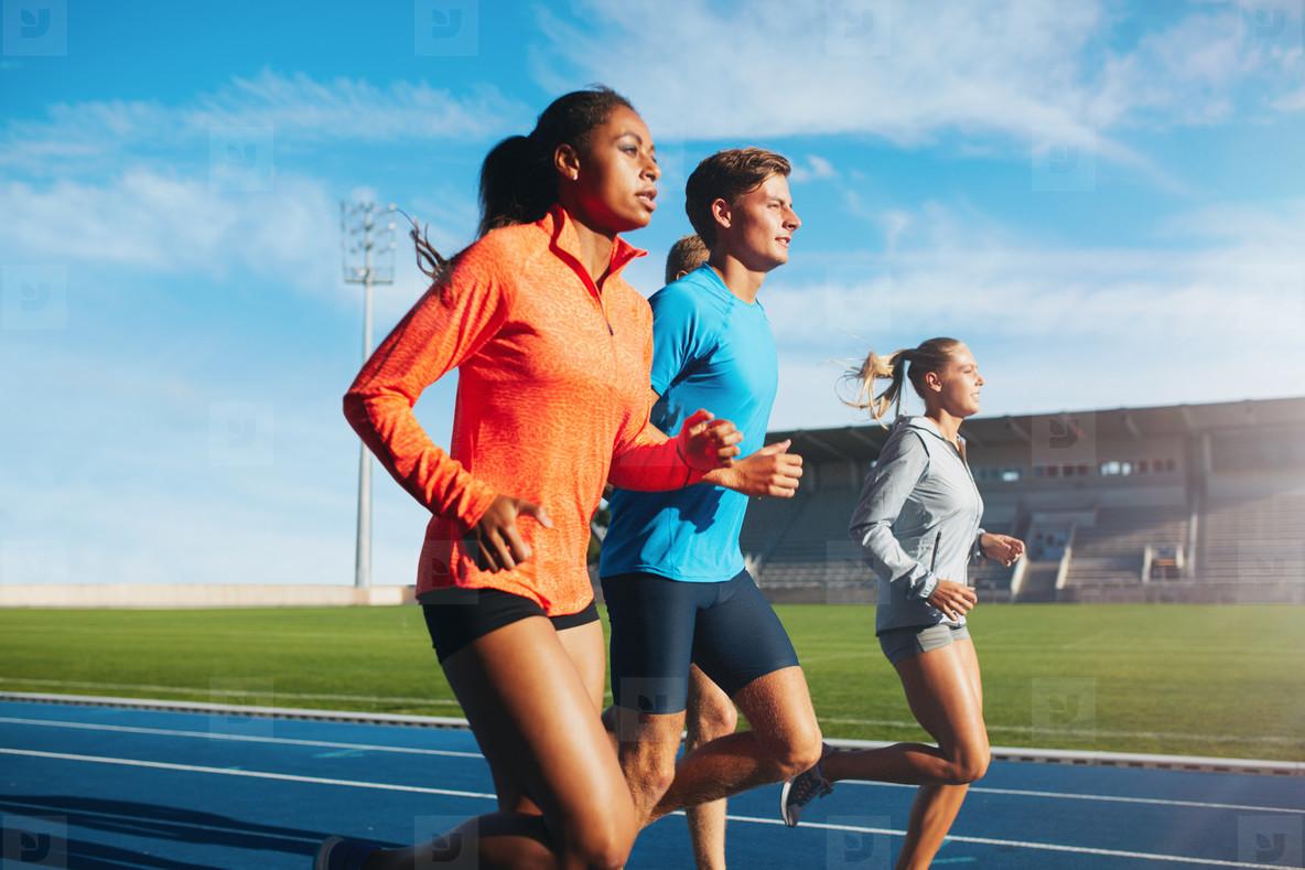 Runners running on race track in stadium