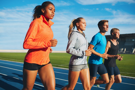 Diverse sports person running on racetrack