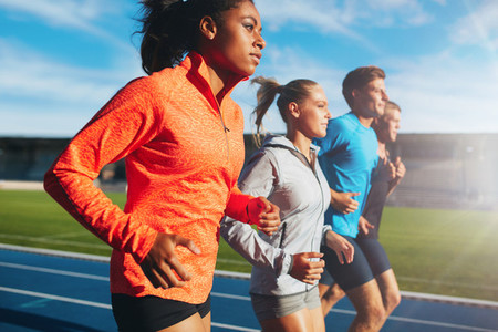 Woman running with her team on racetrack