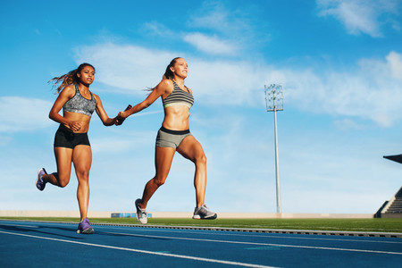 Female relay racing team on racetrack
