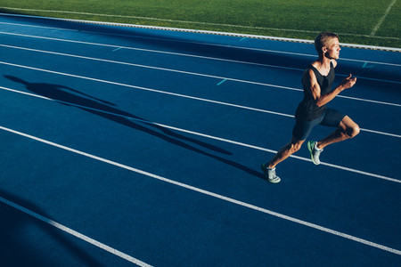 Young professional sprinter on racetrack