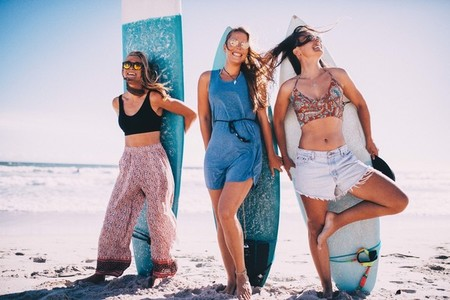 Group of girls having fun with surfboards on beach