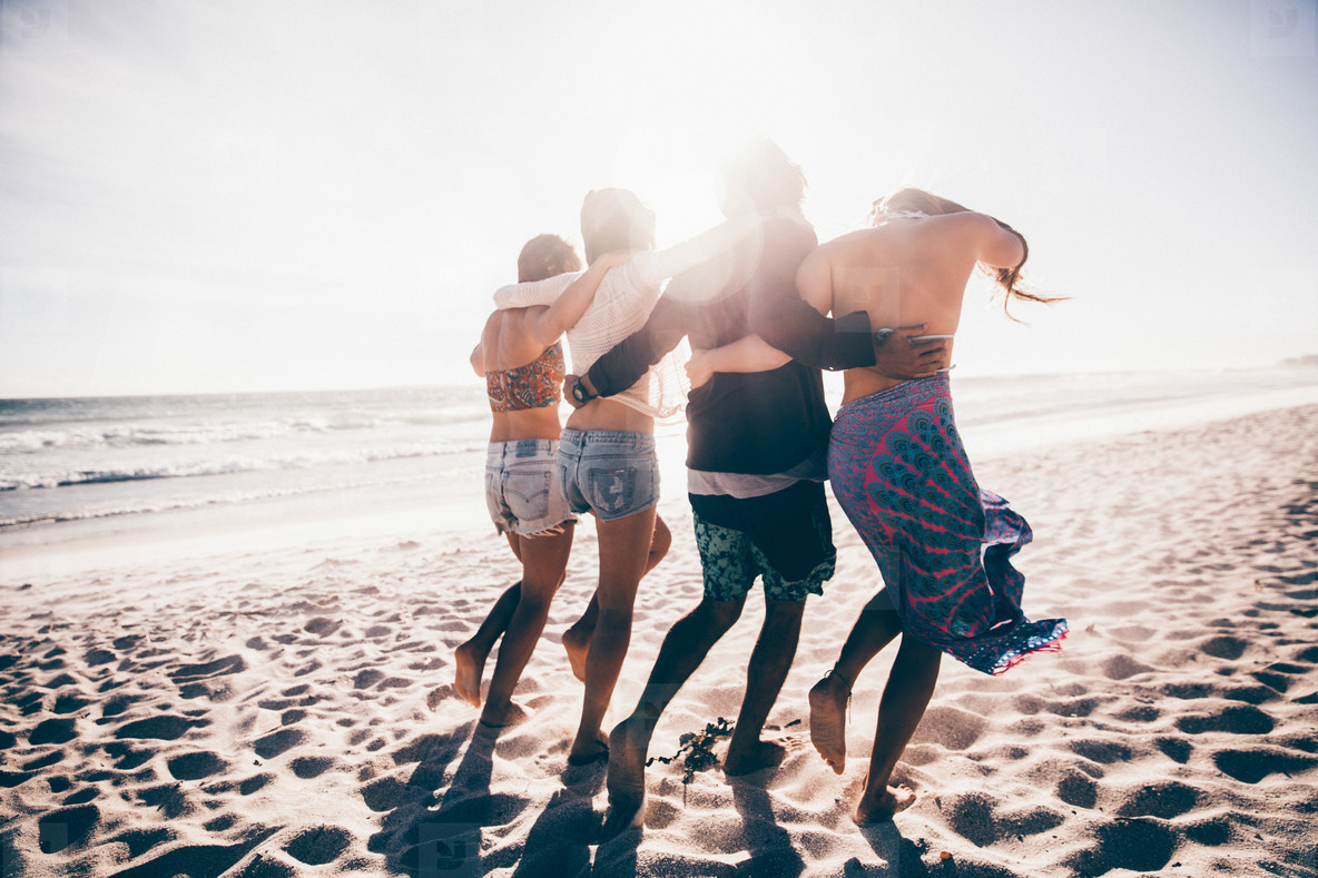Happy group of young adult friends walking on the beach together