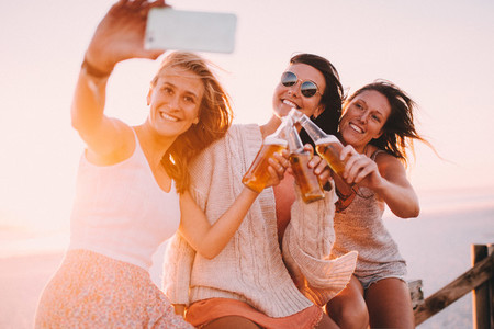 Young adult friends taking selfie on beach party