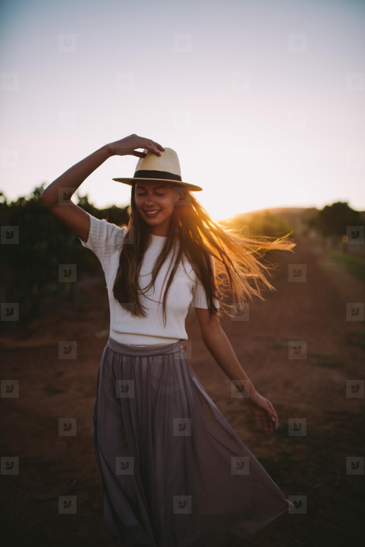 Countrygirl on farmland in sunset