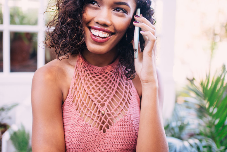 Smiling young adult woman talking on the phone