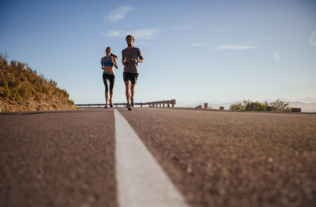 Two young people running on country road
